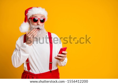 Omg newyear x-mas discounts! Portrait of impressed funky crazy grey hair santa claus in red hat use smart phone read noel christmas information isolated yellow color background