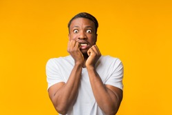 Omg. Scared Afro Guy Looking At Camera Touching Face Posing On Yellow Background. Studio Shot