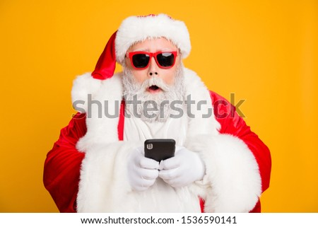 Omg tradition christmas discounts? Close up photo of impressed voiceless funky fat santa claus use smartphone find x-mas sales on internet wear red hat headwear isolated over shine color background