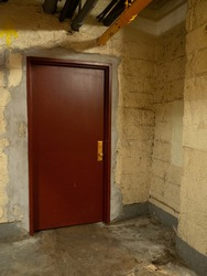 Ominous, dark, dirty corner with locked red door and hanging pipes.