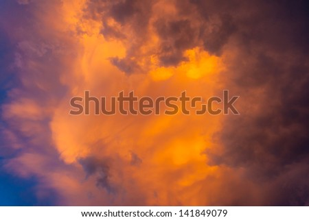 Ominous sky plays with light. sky becomes dark purple clouds. yellow-orange light from the sun breaks through the storm.