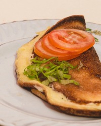 omlette with greans and tomatoes on it