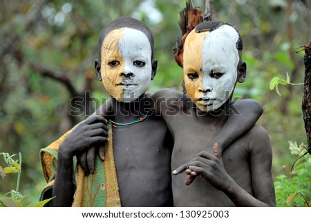 OMO VALLEY, ETHIOPIA - FEB 5: unidentified Surma posing by the river and painting themselves,. Surma in the Omo valley,could disappear because of Gibe III hydroelectric dam on Feb 5, 2013 in Omo Valley, Ethiopia.
