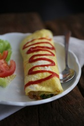 Omurice or omu-rice is an example of yōshoku consisting of an omelette made with fried rice and thin, fried scrambled eggs, usually topped with ketchup. Selective focus.