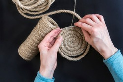 on a black background, hands are knitting a jute basket next to a jute rope, jute twine, knitting an interior basket, a circle of jute is tied
