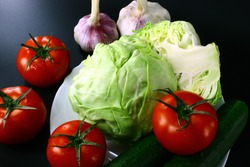 On a black background placed useful vegetables such as - red tomato, garlic, cabbage, cucumbers. Some vegetables lying in a white plate, the part lying next to each other