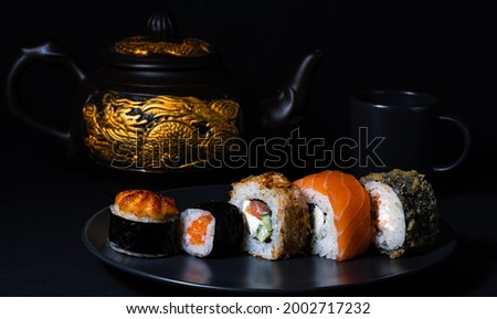 On a black plate sushi set: hot rolls-yaki maki, baked, maki and Philadelphia rolls. In the background a teapot with a golden dragon and a cup. Japanese kitchen