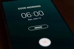 On a black smartphone, an alarm clock rings for 6 am with the inscription Good morning close-up, background