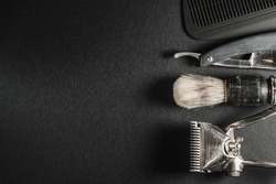 On a black surface are old barber tools.Two vintage manual hair clipper, comb, razor, shaving brush, hairdressing scissors. black monochrome. Close-up. Barbershop background. contrast shadows.