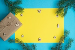 On a blue background, a yellow sheet of paper, fir-tree branches, gift boxes wrapped in kraft paper and wooden figurines for decorating the house for Christmas. flat lay, Concept new year