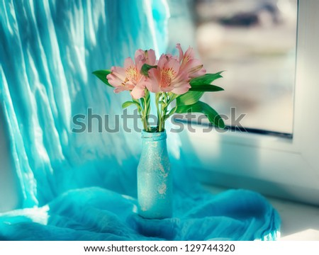 on a blue background and a blue vase delicate ornamental flowers
