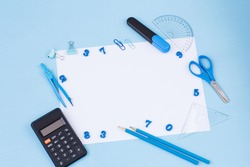 on a blue background, numbers, calculator, ruler, marker, paper clips, compasses, scissors and a white sheet of paper