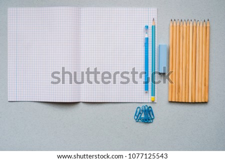 On a blue background, school accessories and a pen, colored pencils, a pair of compasses, a pair of compasses, a pair of scissors. Copy space, top view #1077125543
