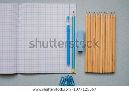 On a blue background, school accessories and a pen, colored pencils, a pair of compasses, a pair of compasses, a pair of scissors. Copy space, top view #1077125567