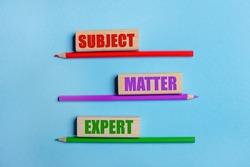 On a blue background, three colored pencils, three wooden blocks with text SUBJECT MATTER EXPERT
