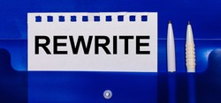 On a blue background, white pens and a sheet of paper with the text REWRITE