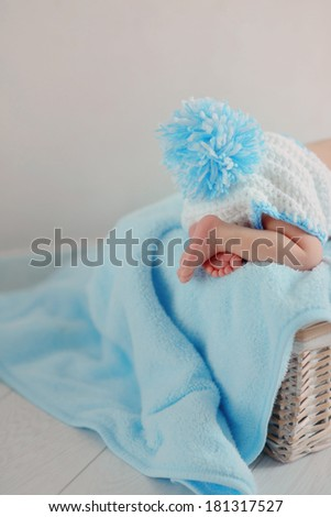 on a blue blanket baby is sleeping with a beautiful blue knitted bubo