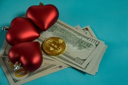 On a blue-green background, a gold bitcoin coin surrounded by red hearts. There is a bitcoin coin surrounded by three hearts on the pack of dollars. The concept of humanity's love for money, wealth.