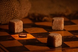 On a chessboard, the battle between coffee beans and brown sugar. you can see a coffee bean and three pieces of brown sugar. The chessboard is classic. The light is directed towards to one coffee bean