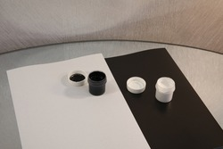 On a clean, light sheet, an open jar of black paint on dark paper stands a container of white watercolors on a mirrored table with a gray wall.Conceptually different close-up variations