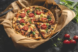 on a dark, stone table stands an old frying pan with pizza in baking paper. Baked and crunchy pizza with roasted tomatoes, cheese, fresh basil, olives and pieces of white meat