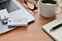 On a desk with a laptop, glasses, coffee, and a notebook, a vocabulary book was placed open There. The word CDN is there. It's an acronym that means Content Delivery Network.