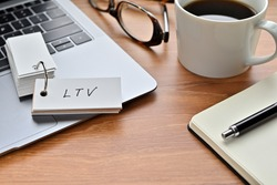 On a desk with a laptop, glasses, coffee, and a notebook, a vocabulary book was placed open There. The word LTV is there. It's an acronym that means Life Time Value.