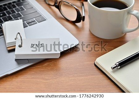 On a desk with a laptop, glasses, coffee, and a notebook, a vocabulary book was placed open There. The word DNS is there. It's an acronym that means Domain Name System. Stock photo ©