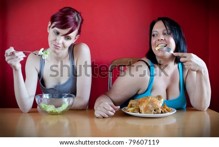 On a diet. Skinny woman eating a few leaves of salad while the overweight woman is eating whole chicken.