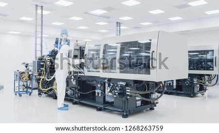 On a Factory Scientist in Sterile Protective Clothing Work on a Modern Industrial 3D Printing Machinery. Pharmaceutical, Biotechnological and Semiconductor Creating / Manufacturing Process.