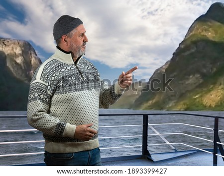 Photo of  On a ferry in the Sognefjord, an elderly Norwegian with a beard is standing on the railing. He wears a typical Norwegian sweater. In the background you can see the high rock walls and a cloudy sky abo