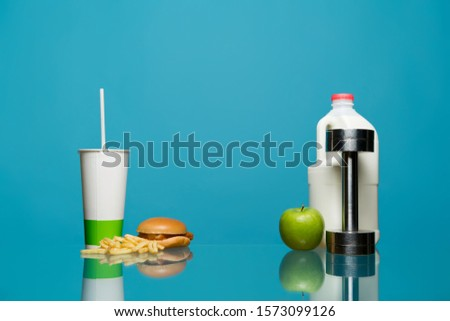 On a glass table are signs and objects of a healthy and not healthy lifestyle. On a glass table are signs and objects of a healthy and not healthy lifestyle. Sports vs. Fast Food