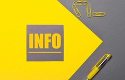 On a gray and yellow background, a gray sticker with yellow text INFO, yellow paper clips and a yellow pen