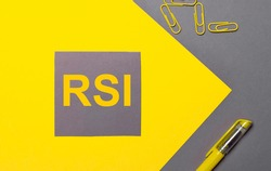 On a gray and yellow background, a gray sticker with yellow text RSI Relative Strength Index, yellow paper clips and a yellow pen