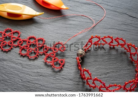 On a gray stone background, close-up of unfinished lace of red thread for a necklace, bright shuttle tatting and a finished bracelet with magnetic snaps. Weaving lace tatting is a type of needlework. Photo stock ©