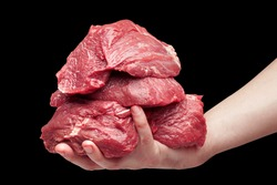 on a hand the mountain of raw beef meat lies. on a black background