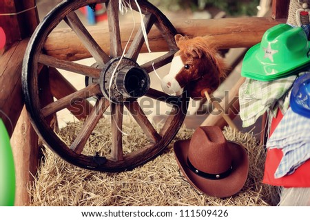 on a haystack the brown cowboy's hat and a wooden wheel with color balloons lies