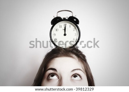 On a head of the girl there is an alarm clock. - stock photo