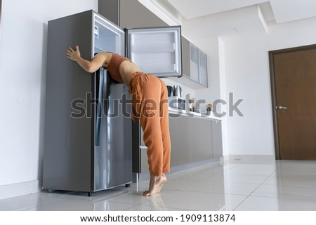 On a hot day, the girl cools with his head in the refrigerator. Broken air conditioner. Foto stock ©