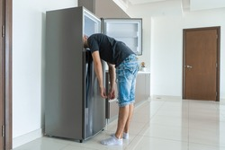 On a hot day, the guy cool down with his head in the refrigerator. Broken air conditioner.
