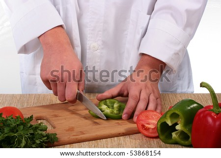 On a kitchen board green pepper and the man the cook knifes it.
