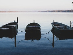 on a large lake there are many rowing boats moored to the shore