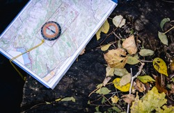 On a large stone lies a tourist topographic map with a compass. Near them autumn leaves are scattered