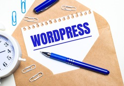 On a light background, a craft envelope, an alarm clock, paper clips, a blue pen and a sheet of paper with the text WORDPRESS.