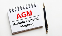 On a light background, a white notebook with are words AGM Annual General Meeting and a pen.