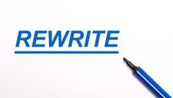 On a light background, an open blue felt-tip pen and the text REWRITE