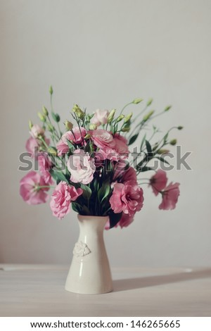 on a light background elegant vase with a bouquet of pink flowers