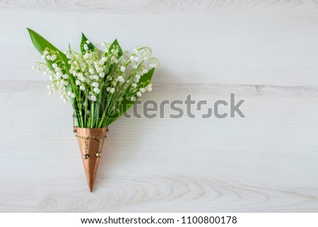 on a light background in a bronze old vase a bouquet of lilies of the valley #1100800178