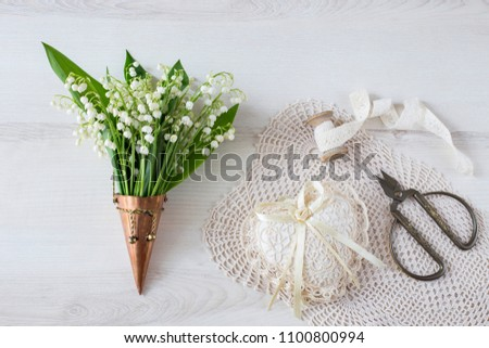 on a light background in a bronze old vase a bouquet of lilies of the valley, a heart made of lace, scissors and a ribbon #1100800994