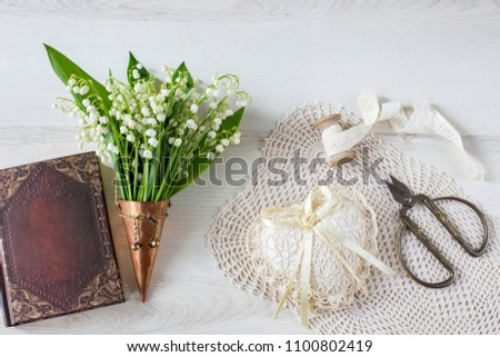 on a light background in a bronze old vase a bouquet of lilies of the valley, a heart made of lace, scissors, a ribbon and book #1100802419